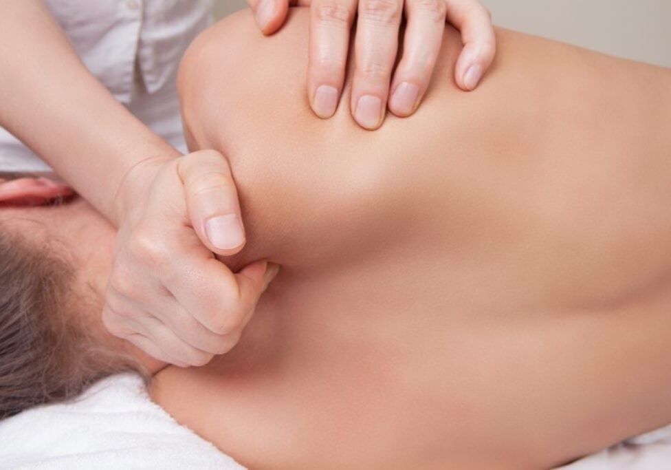 Professional  therapist doing neck and shoulder deep tissue and sport massage